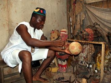 Togolese voodoo priest holds soccer ball while practicing voodoo in Lome